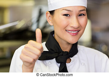 Portrait of smiling female cook gesturing thumbs up -...