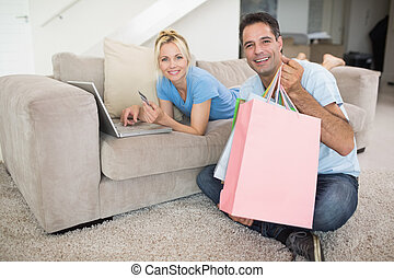 Portrait of a smiling couple doing online shopping at home