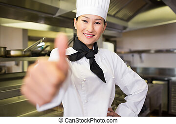 Smiling female cook gesturing thumbs up in kitchen -...