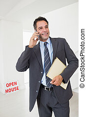 Real estate agent with documents using mobile phone