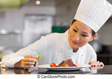 Concentrated female chef garnishing food in kitchen -...