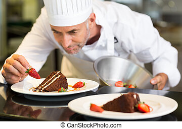 Concentrated male pastry chef decorating dessert - Closeup...