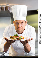 Smiling male chef with cooked food