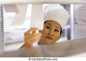 Female chef going through cooking checklist at kitchen -...