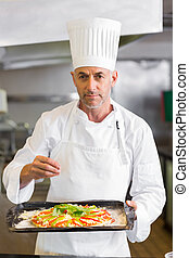 Confident chef holding cooked food in kitchen - Portrait of...