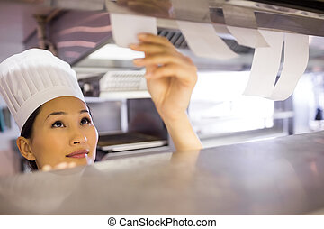 Female chef going through cooking checklist at kitchen -...