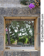 Stone Wall Opening with pink flower. Mallorca, Balearic...
