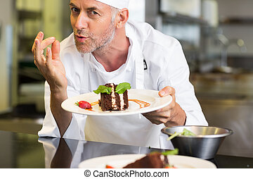 Smiling male pastry chef with dessert in kitchen - Closeup...