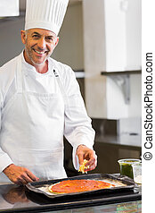 Smiling male chef garnishing food in kitchen - Portrait of a...