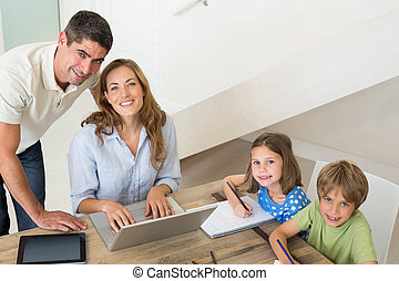 Children coloring while parents using laptop - High angle...