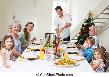 Family having Christmas meal at dining table - Portrait of...