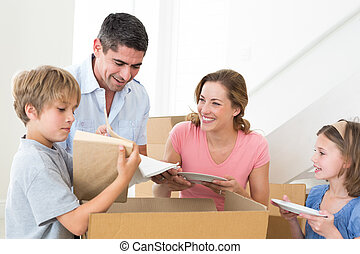Family unpacking cardboard box in house