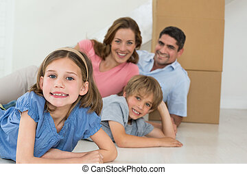 Happy family lying in their new house