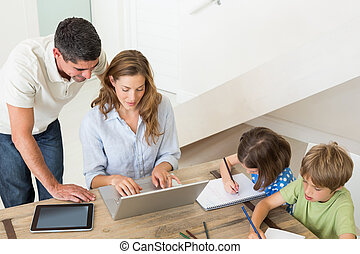 Parents using laptop while children coloring at home