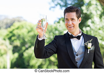 Groom toasting champagne flute in g - Happy young groom...