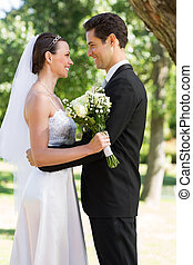 Newly wed couple looking at each other in garden