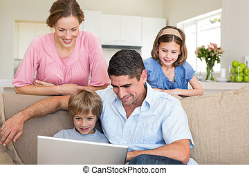 Family using laptop - Father with boy using laptop while...