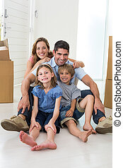 Family sitting on floor in new house - Portrait of happy...