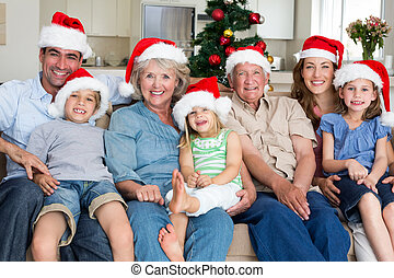 Family in Santa hats celebrating Christmas - Portrait of...