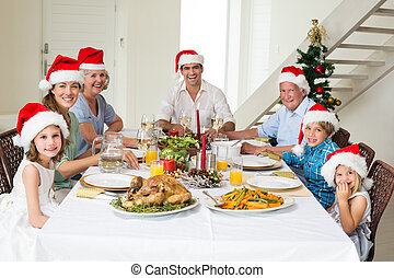 Happy family in Santa hats having Christmas meal - Portrait...
