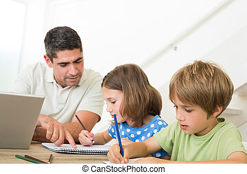 Father with laptop assisting children drawing at home