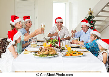 Family toasting wine while having Christmas meal -...
