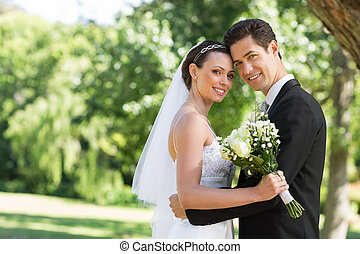 Loving newly wed couple in garden - Portrait of loving newly...