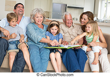 Family reading storybook at home - Happy multigeneration...