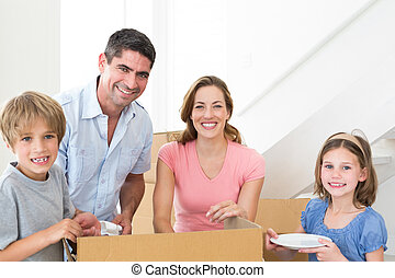 Happy family unpacking cardboard box in house - Portrait of...