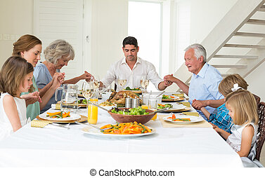 Family praying together before meal at dining table -...