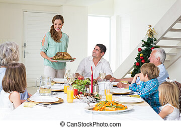 Mother serving Christmas meal to family at dining table