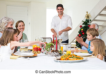 Family enjoying Christmas meal at dining table - Happy...