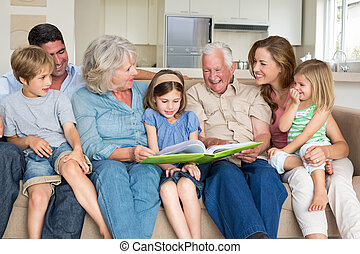 Family reading storybook in living room - Multigeneration...