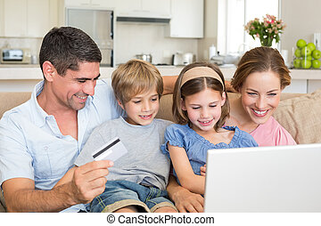 Family shopping online - Happy family of four shopping...