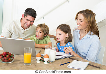 Family using laptop while having breakfast at home