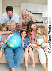 Family exploring globe in living room