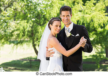 Smiling bride and groom dancing in garden - Portrait of...