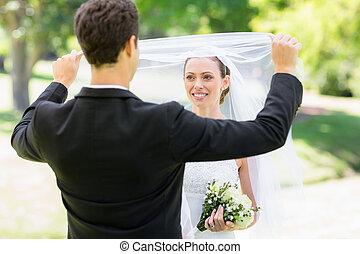 Loving groom lifting veil of bride - Young loving groom...