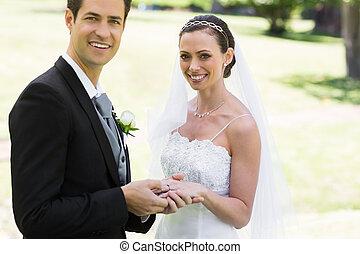 Groom placing ring on brides finger at park - Portrait of...