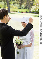 Loving groom lifting veil of bride - Young loving groom...