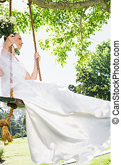 Thoughtful bride swinging in garden - Thoughtful young bride...