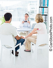 Expectant couple consulting gynaecologist - Expectant couple...