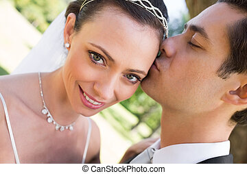 Bride being kissed by groom in garden - Portrait of young...
