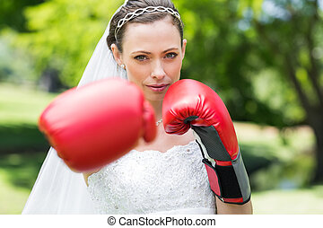 Bride with boxing gloves punching in park - Portrait of...