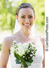 Happy young bride with flowers in garden