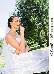 Young bride sitting in garden
