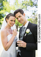 Beautiful bride and groom holding champagne flutes -...