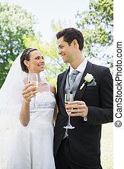 Romantic bride and groom having champagne in park - Romantic...