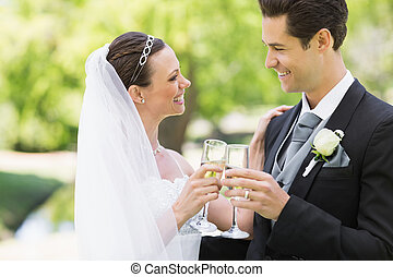 Newlywed couple toasting champagne in park