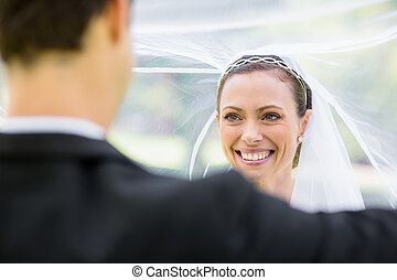 Young groom lifting bridal veil in garden
